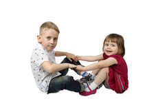 Little boy and girl sit on floor and hold each others hands. Isolated on white background with shadow Royalty Free Stock Photos