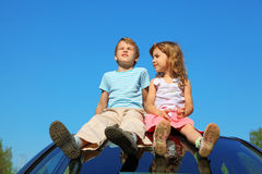 Little boy and girl sitting on car roof Royalty Free Stock Photo