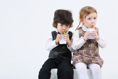 Little boy and girl sitting and drink juice Stock Photography