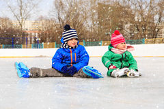 Little boy and girl sitting on ice with skates Royalty Free Stock Photos