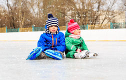 Little boy and girl sitting on ice with skates Stock Image