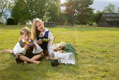 Little boy and girl sitting on a lawn Stock Images