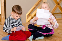 Little boy and girl sitting together reading. Little boy and girl sitting together on a wooden floor each reading a letter or note on a sheet of paper with Stock Photos