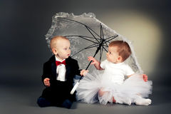 Little boy and girl sitting under umbrella Royalty Free Stock Photos