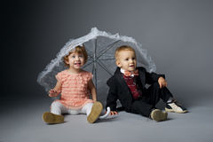 Little boy and girl sitting under umbrella Royalty Free Stock Images