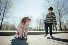 Little boy and girl skaiting on the street Stock Image