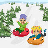 Little boy and girl sliding down hill on tubes Royalty Free Stock Photos