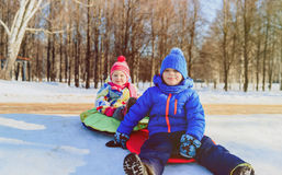 Little boy and girl sliding in winter snow Royalty Free Stock Photography