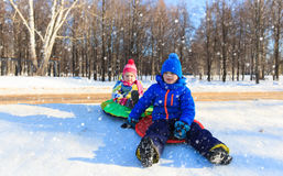 Little boy and girl sliding in winter snow Royalty Free Stock Photo