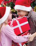 Little boy and girl smiling with present near the Christmas tree Royalty Free Stock Photography