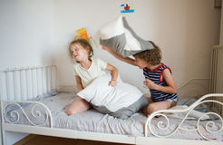 Little boy and girl staged a pillow fight on the bed in the bedroom. Stock Image