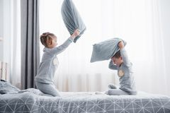 Little boy and girl staged a pillow fight on the bed in the bedroom. Naughty children beat each other pillows. They like. That kind of game stock images