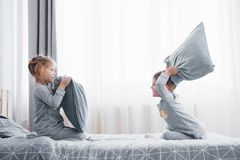 Little boy and girl staged a pillow fight on the bed in the bedroom. Naughty children beat each other pillows. They like. That kind of game royalty free stock photography
