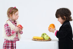 Little boy and girl stand and hold fruits Stock Photo