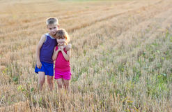 Little boy and girl standing on field  and hugging Stock Image