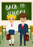 Little boy and girl standing in front of classroom chalkboard. Back to school concept Stock Image