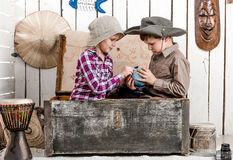 Little boy and girl study globe in big chest Royalty Free Stock Photography