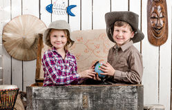 Little boy and girl study globe in big chest Royalty Free Stock Images