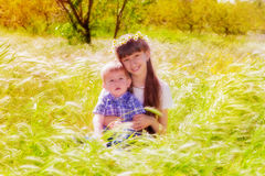 Little boy and girl in the summer field with flowers Stock Photos