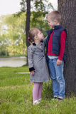 Little boy and girl on a sunny day standing on green grass near Stock Photos