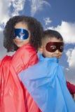 Little boy and girl superheros against blue sky Stock Photos