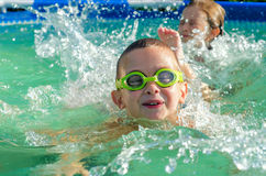 Little boy and girl swimming in swimming pool on sunny summer day Stock Images