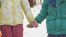 Little boy and girl taking hands friendly. The little boy and the little girl standing each other taking hands on outdoors in winter stock footage