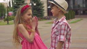 Little boy and girl talk outdoors. Cute little boy and girl talking on the walkway outdoors. Pretty caucasian girl raising her hands to the sides. Handsome male stock video footage
