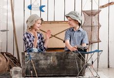 Little boy and girl talk sitting in chest. Little boy and girl talk sitting in big old chest Royalty Free Stock Photos
