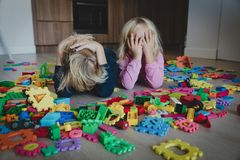 Little boy and girl tired stressed exhausted with toys scattered indoors. Kids bored being home royalty free stock photo