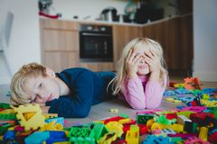Little boy and girl tired stressed exhausted with toys scattered indoors. Kids bored being home royalty free stock photography