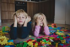 Little boy and girl tired stressed exhausted with toys scattered indoors. Kids bored being home royalty free stock photos