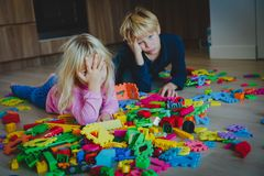 Little boy and girl tired stressed exhausted with toys scattered indoors. Kids bored being home stock photography