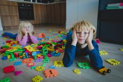 Little boy and girl tired stressed exhausted with toys scattered indoors. Kids bored being home stock images