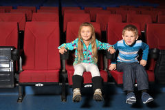 Little boy and girl together watching a movie Stock Photo