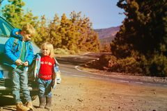 Little boy and girl travel by car on the road. In nature Royalty Free Stock Image