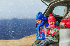Little boy and girl travel by car in winter mountains Stock Photos