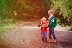 Little boy and girl travel hiking in nature looking at map. Travel concept stock photo