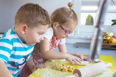 Little boy and girl twins with rolling pin. Preparing Christmas cookies royalty free stock photography