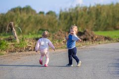 Little boy and girl twins running on the road on Crete. Greece stock photo