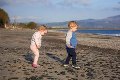 Little boy and girl twins walking on the beach of Crete. Greece royalty free stock photos
