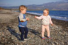 Little boy and girl twins walking on the beach of Crete. Greece stock images