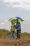 Little boy and girl with umbrella. Little boy kiss girl, under umbrella in autumn day Stock Photography