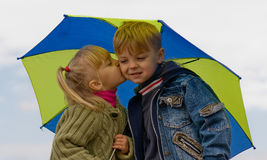 Little boy and girl with umbrella Stock Photos