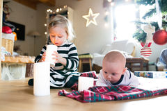 Little boy and girl under Christmas tree, girl playing with cand Stock Photos