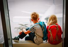 Little boy and girl waiting for plane in airport. Family travel stock photo