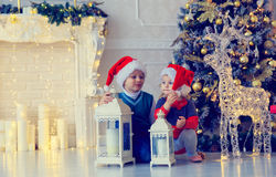 Little boy and girl waiting for presents in decorated living room Stock Photos