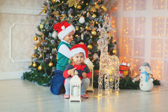 Little boy and girl waiting for presents in decorated living room Stock Photography