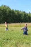 Little boy and girl walk on grass at green meadow Royalty Free Stock Image