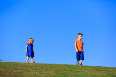 Little boy and girl walking against blue sky Stock Photography